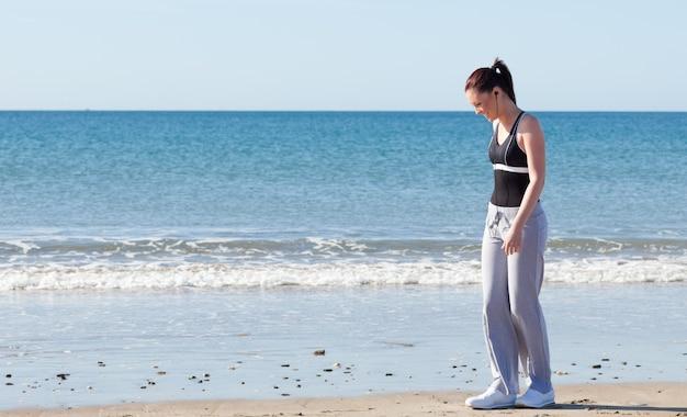 Mulher brilhante de pé na praia e ouvindo música