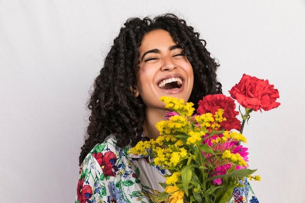 Mulher brilhante rindo com ramo de flores