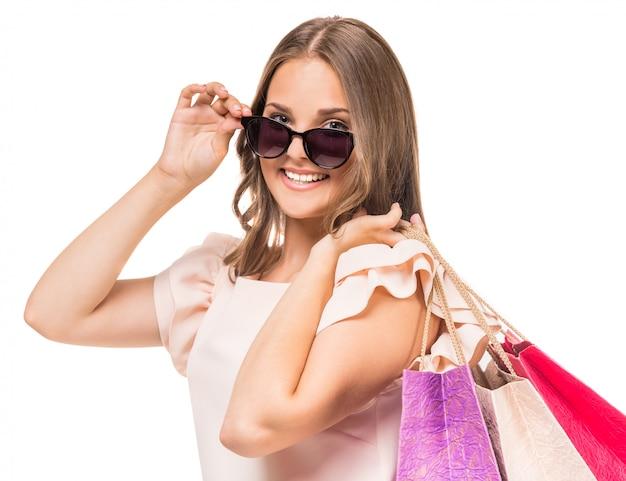 Mulher brincalhão em óculos de sol segurando sacolas coloridas.