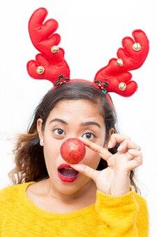 Mulher brincalhão que cobre o nariz com a bola do natal