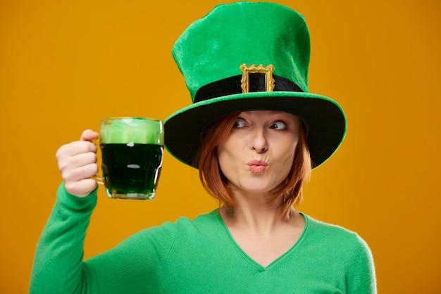 Mulher brincalhona com chapéu de duende olhando para a cerveja