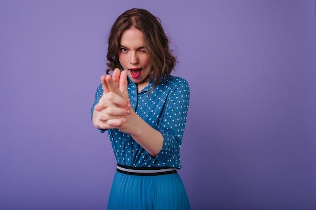 Mulher brincalhona de cabelos curtos em trajes da moda, posando na parede roxa. modelo feminina bem-humorada com cabelos ondulados brincando