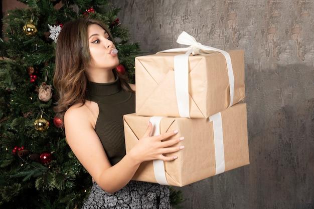 Mulher brincalhona olhando para os presentes de natal na frente de uma árvore de pinha