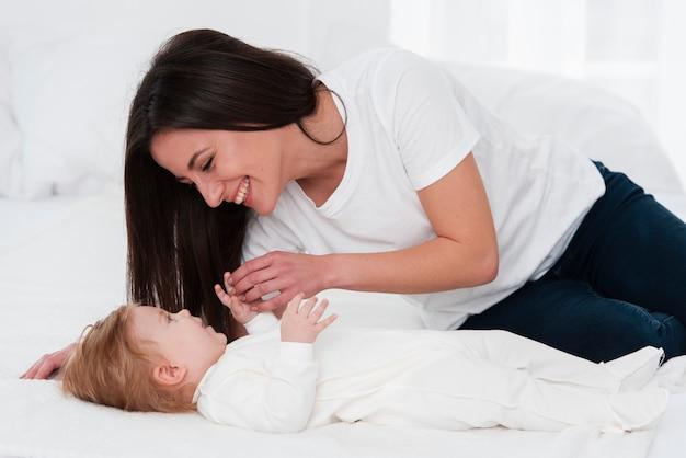 Mulher brincando com bebê na cama
