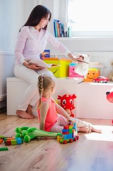 Mulher brincando com criança na sala de jogos
