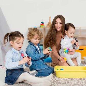 Mulher brincando com crianças com o cubo de rubik