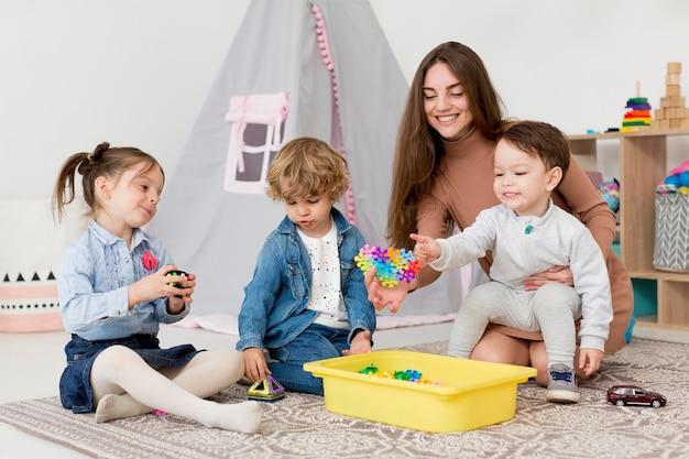 Mulher brincando com crianças e brinquedos em casa