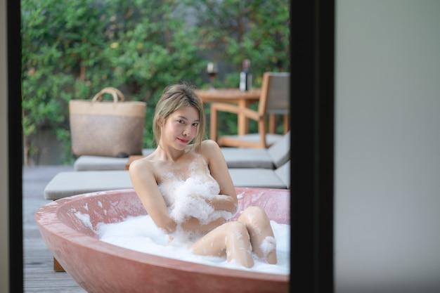 Mulher brincando com espuma de espuma enquanto toma banho na banheira.