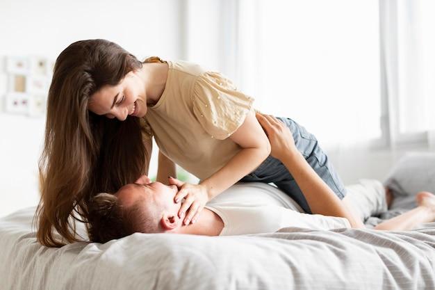 Mulher brincando com o marido na cama