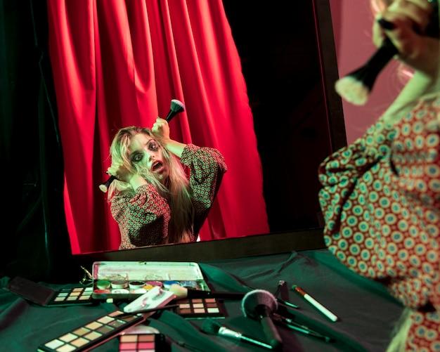 Mulher brincando com pincéis de pó no espelho