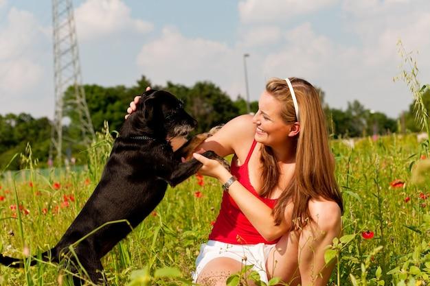 Mulher brincando com seu cachorro em um prado