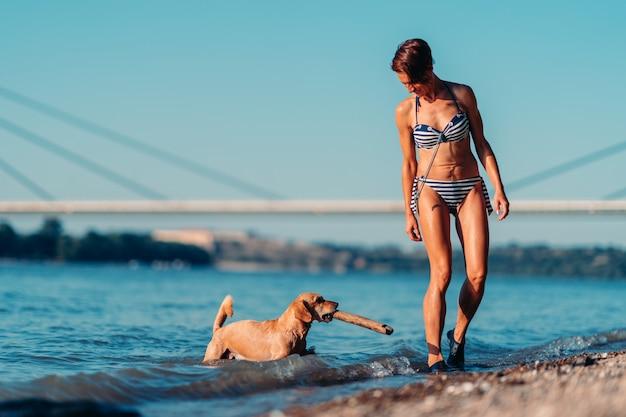 Mulher brincando com um cachorro à beira do rio