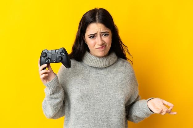 Mulher brincando com um controlador de videogame isolado no amarelo, fazendo gestos de dúvida enquanto levanta os ombros