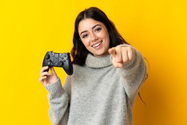 Mulher brincando com um controle de videogame isolado na parede amarela apontando o dedo para você com uma expressão confiante