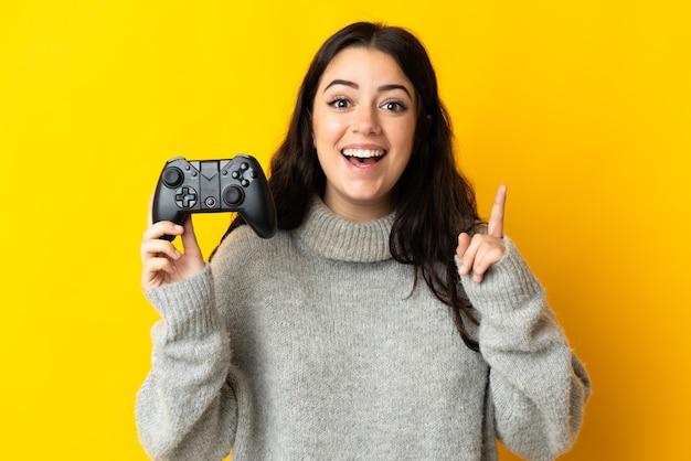 Mulher brincando com um controle de videogame isolado na parede amarela apontando uma ótima ideia
