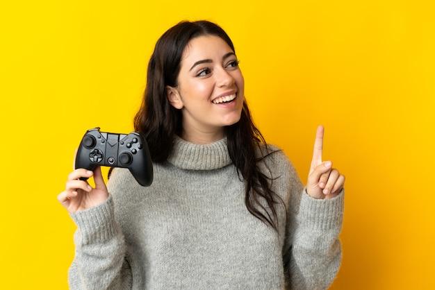 Mulher brincando com um controle de videogame isolado na parede amarela com a intenção de perceber a solução enquanto levanta um dedo