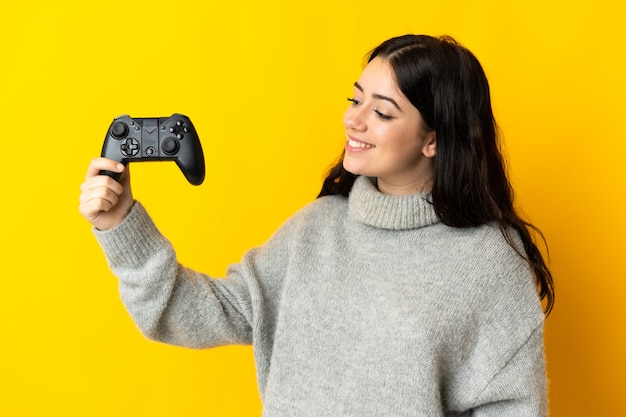 Mulher brincando com um controle de videogame isolado na parede amarela com uma expressão feliz