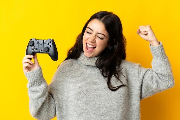 Mulher brincando com um controle de videogame isolado na parede amarela comemorando uma vitória