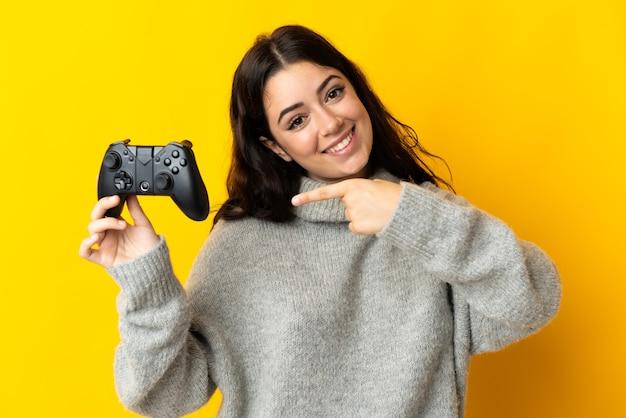 Mulher brincando com um controle de videogame isolado na parede amarela e apontando-o