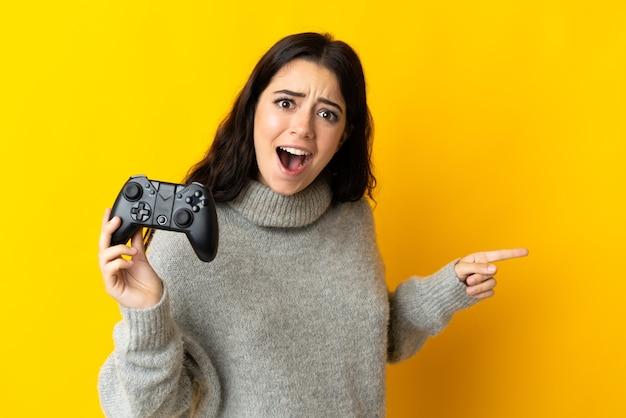 Mulher brincando com um controle de videogame isolado na parede amarela surpresa e apontando o dedo para o lado