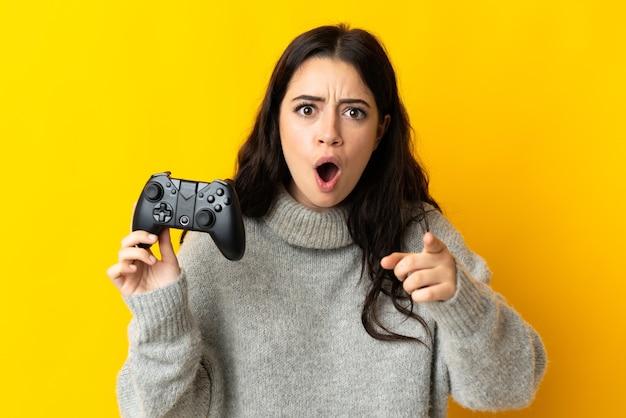 Mulher brincando com um controle de videogame isolado na parede amarela surpresa e apontando para a frente