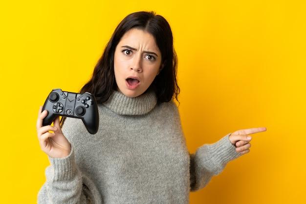 Mulher brincando com um controle de videogame isolado na parede amarela surpresa e apontando para o lado