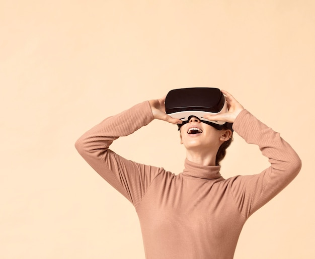 Mulher brincando com um fone de ouvido de realidade virtual e olhando para cima