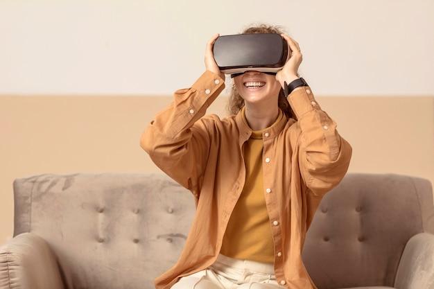 Mulher brincando com um fone de ouvido de realidade virtual e sorrindo