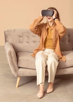 Mulher brincando com um fone de ouvido de realidade virtual, sentada no sofá
