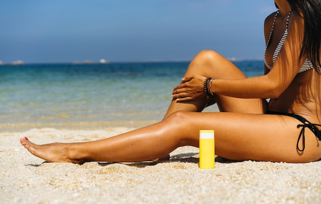 Mulher bronzeada aplicando protetor solar nas pernas bronzeadas em uma praia paradisíaca
