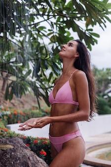 Mulher bronzeada caucasiana em forma bonita tomando banho ao ar livre em dia nublado.