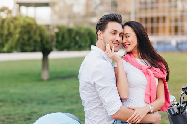 Mulher bronzeada com lindo sorriso tocando a bochecha do namorado com os olhos fechados