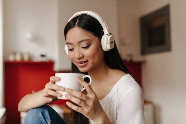 Mulher bronzeada de cabelos escuros bebe chá e ouve música com fones de ouvido enquanto está sentada na cozinha
