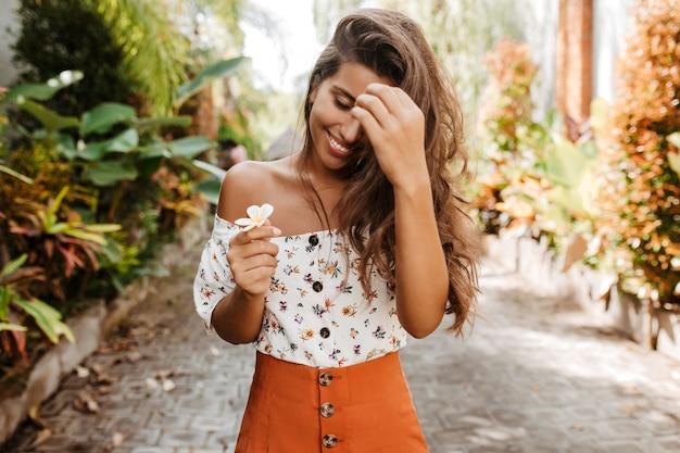 Mulher bronzeada de férias olhando para uma flor branca com um sorriso