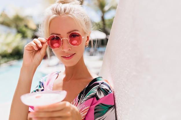 Mulher bronzeada elegante tocando seus óculos de sol rosa