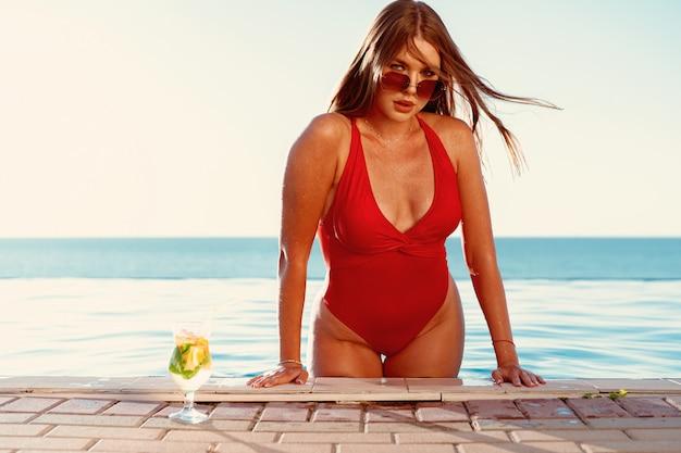 Mulher bronzeada em biquíni vermelho em uma piscina com cocktail