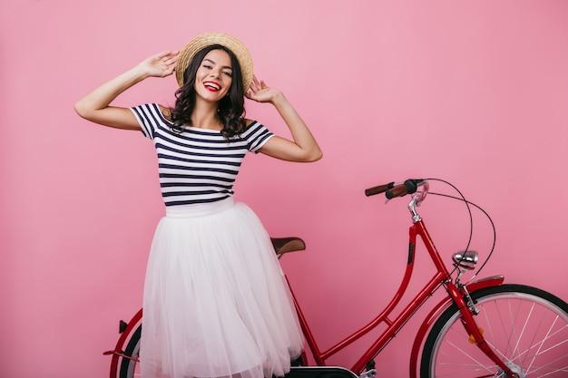 Mulher bronzeada em êxtase tocando seu chapéu de palha. garota caucasiana relaxada posando com bicicleta.