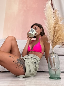 Mulher bronzeada em forma com corpo perfeito em shorts e biquíni segurando uma caneca