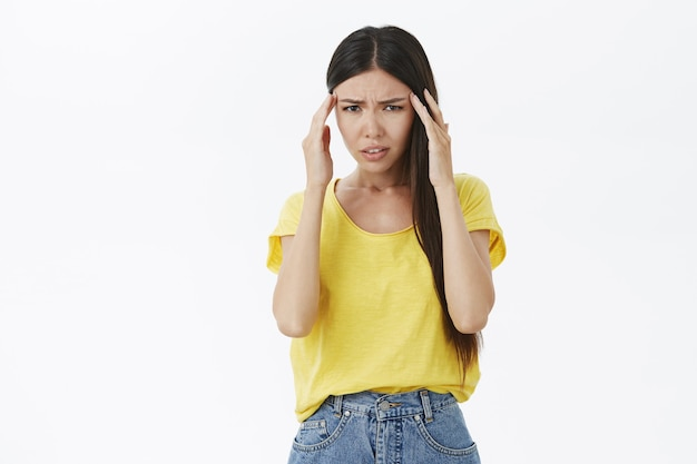 Mulher bronzeada frustrada, desfocada e confusa, com uma camiseta amarela, segurando os dedos nas têmporas.
