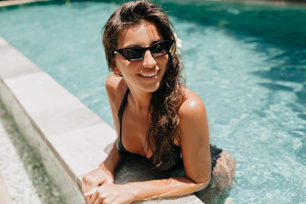 Mulher bronzeada jovem e sorridente, se divertindo e posando na piscina em um dia ensolarado no resort spa tropical.