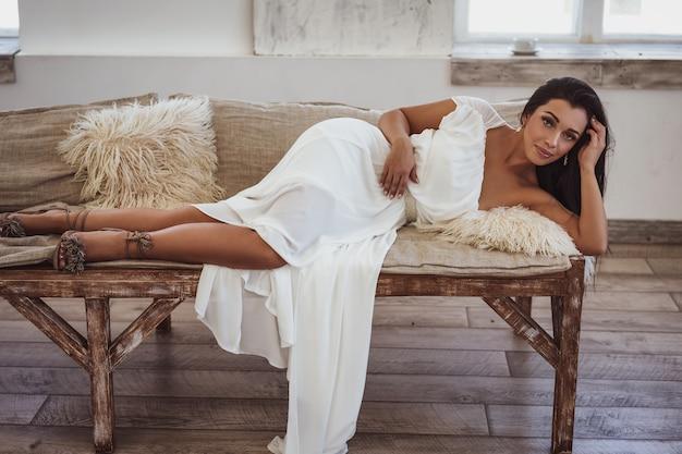 Mulher bronzeada linda deitada na cama em um vestido branco.