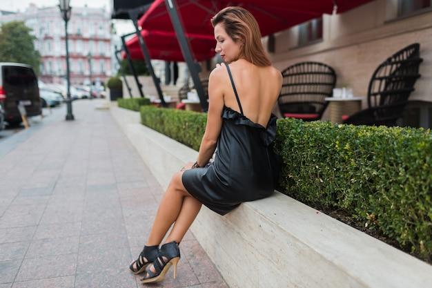 Mulher bronzeada magro em elegante vestido preto e saltos altos com cabelos loiros brilhantes, posando na velha cidade europeia, perto de restaurante de luxo.