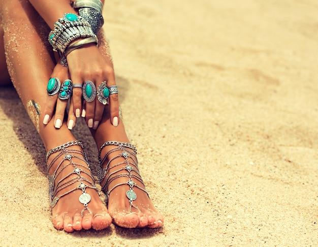 Mulher bronzeada nas mãos e nos pés com manicure e pedicure branca decorada com pulseiras e anéis de prata