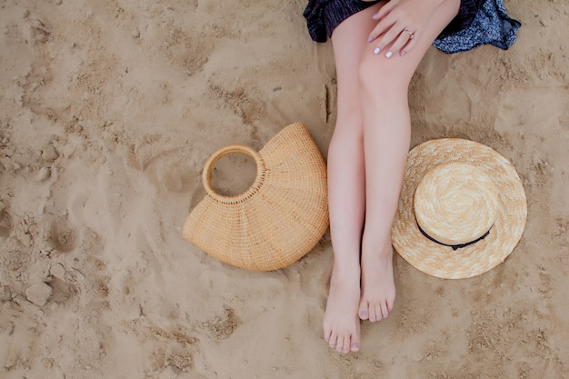 Mulher bronzeada pernas, chapéu de palha e bolsa na praia de areia. conceito de viagens. relaxando na praia, com os pés na areia.