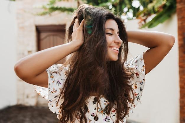 Mulher bronzeada positiva com um sorriso tocando seu cabelo e posando contra a parede da casa com uma porta de madeira