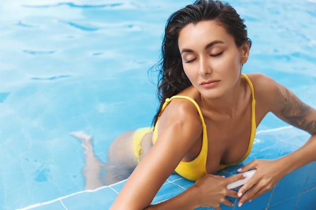 Mulher bronzeada sensual e relaxada de biquíni, olhos fechados, curtindo a piscina.