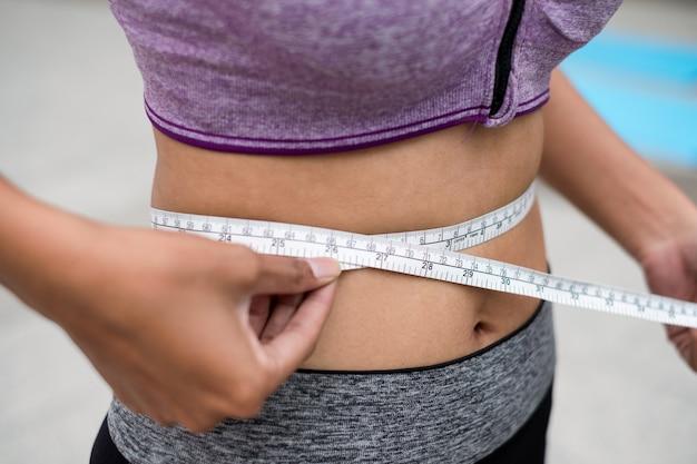 Mulher bronzeada usando barra esportiva usando alça de medição em volta da cintura do corpo
