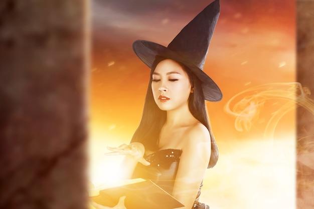 Mulher bruxa asiática com livro de feitiços mostrando magia na mão com fundo dramático