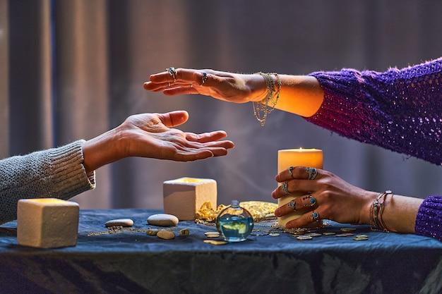 Mulher bruxa cigana durante o ritual de quiromancia e adivinhação em torno de velas e outros acessórios mágicos. ilustração mágica