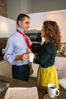 Mulher cacheada ajustando a gravata de um empresário sorridente enquanto toma um café da manhã rápido antes de ir para o trabalho